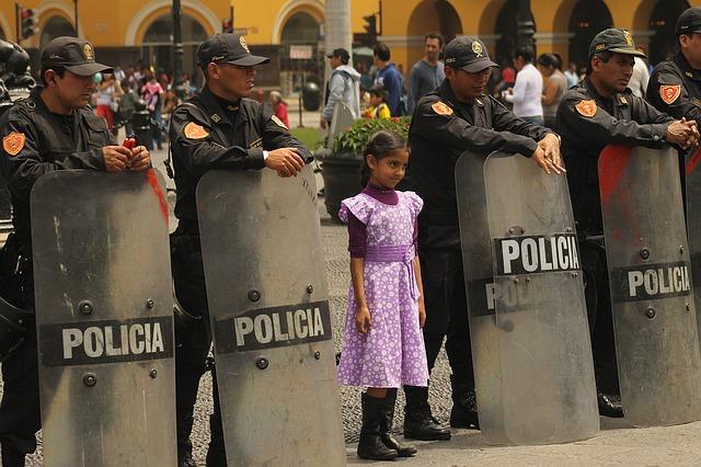 진압경찰과 같이 서 있는 소녀