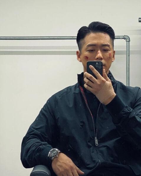 짦은머리남자의모습-핸드폰으로사진을찍는모습