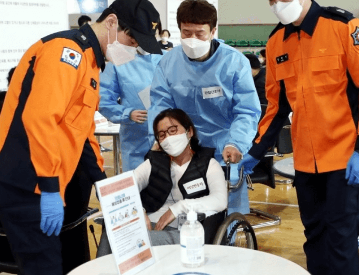 소방관과 의사에게 둘러쌓여 쓰러져 있는 여성